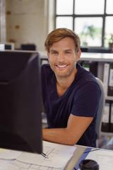 lächelnder mitarbeiter sitzt am schreibtisch im büro