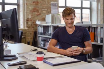 junger mann im büro schaut lächelnd auf sein handy