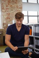junger geschäftsmann im büro arbeitet am tablet
