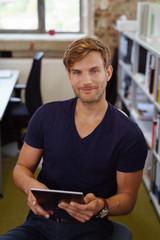 mann sitzt im büro am schreibtisch und hält sein tablet in der hand