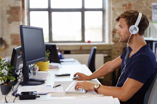 mitarbeiter arbeitet mit kopfhörern in einem modernen büro