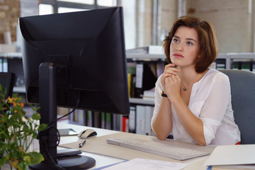 junge frau im büro schaut konzentriert auf den computer