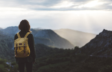Hipster young girl with bright backpack enjoying sunset on peak of foggy mountain. Tourist traveler on background valley landscape view mockup. Hiker looking sunlight in trip, mock up for text