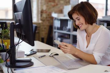 junge frau im büro schaut lachend auf ihr mobiltelefon