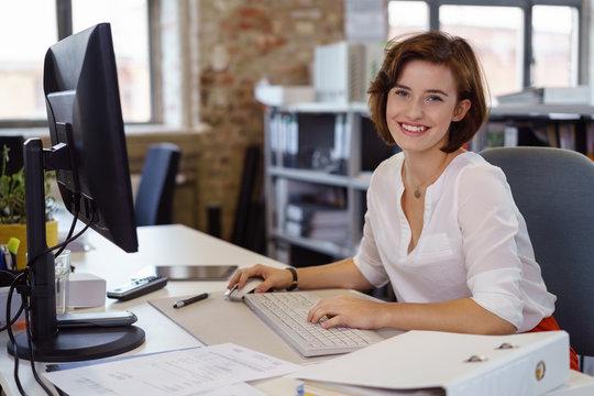 lächelnde junge angstellte im büro