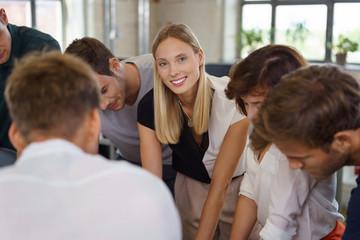 junge blonde frau im büro mit ihren kollegen in einer besprechung