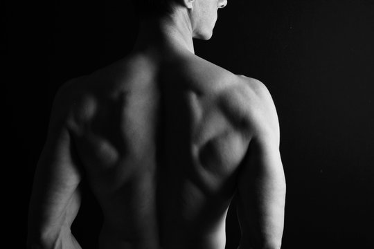 Strong muscular athletic man back on dark background, low key image, copy space