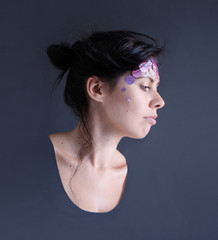 photo portrait of the head of dark haired model with sequins on her forehead