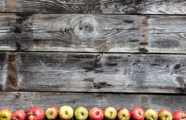 border of organic apples on old genuine wood, flat lay