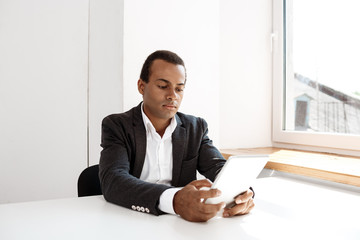 Young successful african businessman looking at tablet, sitting  workplace.