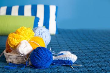 Coloured wool yarn lies in a white basket. Blue plaid.