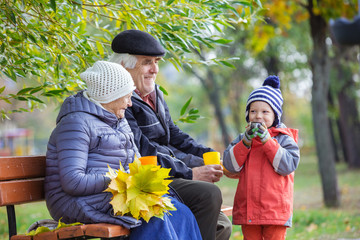 Grandparents and grandson drinking hot tea in autumn park