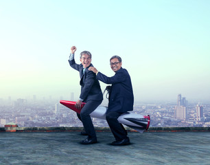 two asian business man funny playing with rocket missile on buil