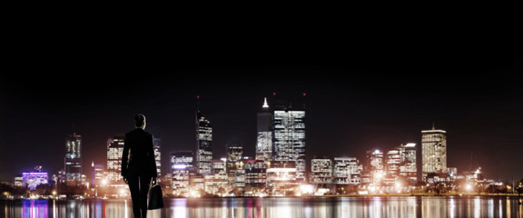 Businesswoman viewing night glowing city