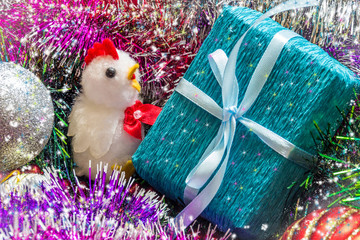 Year of the rooster. Chicken and gift box among the tinsel. Christmas picture