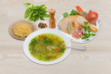 Chicken soup in white dish and ingredients for its cooking