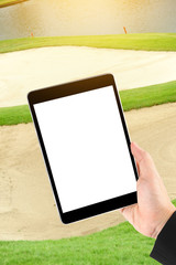 Touch screen in hand, tablet on golf club - soft blur background