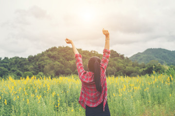 Young happy woman raising hands in yellow flower field on sunset