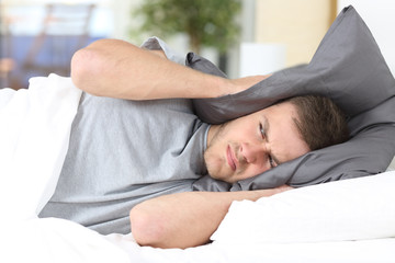 Man trying to sleep covering ears for noise