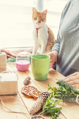 Woman drinking hot chocolate and wrapping eco Christmas gifts brown paper, string and natural branches and decor elements on wooden table at home