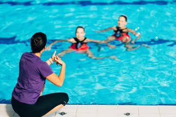 Synchronized Swimmers with trainer. Performance in the pool with trainer