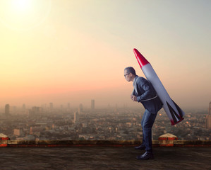 business man carries rocket missile on high building roof  again