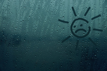 Rain drop on glass window with Sad face, Sadness or Need Sunshine Concept