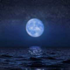 Full moon rising over empty ocean at night, blur background