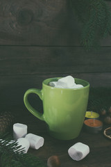 Hot chocolate with marshmallow in green cup with Christmas and New Years decor on dark wooden background