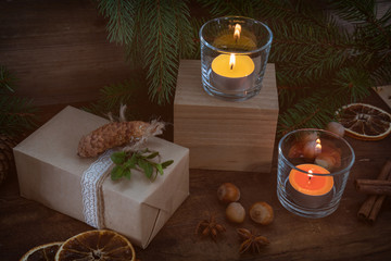 Eco Christmas packages gift and two light candles with Christmas and New Years decor and Christmas tree on dark wooden background