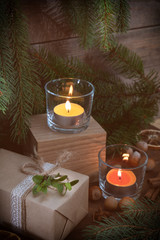 Two light candles with Christmas and New Years decor and Christmas tree on dark wooden background