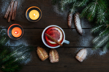 Hot tea with lemon and cinnamon in white cup. Two light candles, Christmas tree and cookies on dark wooden background. Top view.