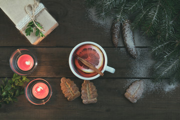 Hot tea with lemon and cinnamon in white cup. Eco Christmas packages gift. Two light candles, Christmas  tree and cookies on dark wooden background. Top view.