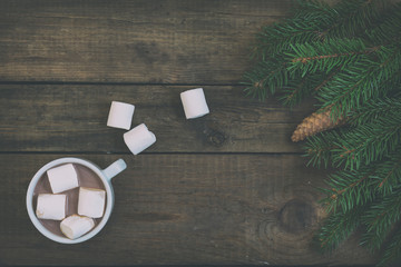 Hot chocolate with marshmallow in white cup and Christmas tree with cone on dark wooden background. Top view. Toned