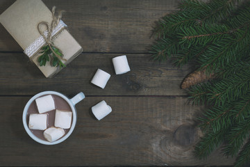 Hot chocolate with marshmallow in white cup,  eco Christmas packages gift and Christmas tree with cone on dark wooden background. Top view. Toned