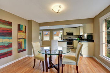 Modern dining area with glass table. Hardwood floor.