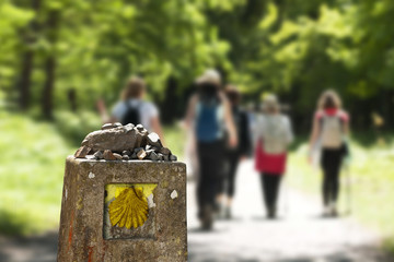 shell scallop sign mark with unfocused pilgrims  in Way of St James, Camino de Santiago, to Compostela Fototapete