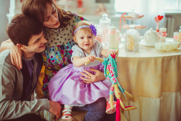 Girl in violet dress holds in her hands a toy rabbit while sitti