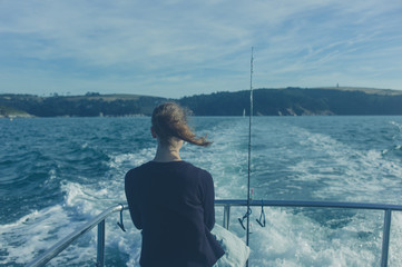 Woman fishing from boat in summer