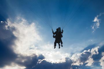 Lot Paralotnią w zachmurzonym niebie w kierunku słońca