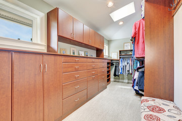 Large walk-in closet with cabinets and carpet floor