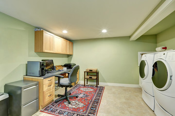 Basement room with home office area and laundry appliances