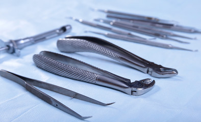 Close up of four different stainless steel surgical forceps and scalpel isolated on white background