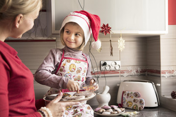 Mother decorating cookies with her little daughter
