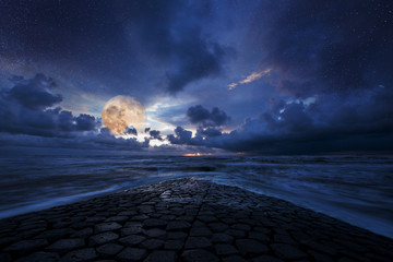 Fantastic stars and moon night over a stone road into the ocean