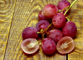 Red rose grapes bunch on wood background. Grapes cut in half.