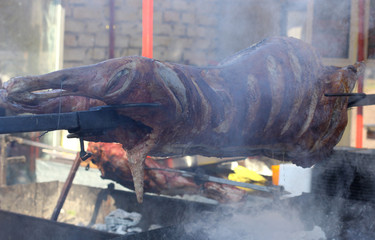 Carcass of a whole pork roasting on a spit over hot coals at an outdoor catered event or food market