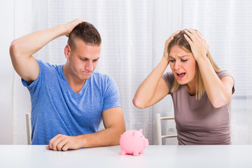 Young couple is in panic because they are having problem with saving money.