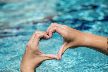 young man shows love sign with heart shape formed by hands