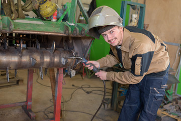 happy apprentice welder at work in the plant